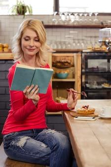 Mulher lendo um livro e comendo um bolo