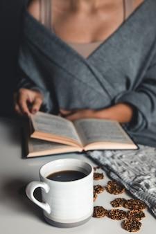 Mulher lendo um livro e tomando café da manhã