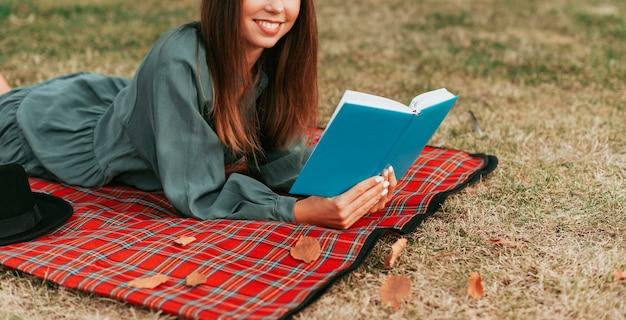 Mulher lendo um livro em uma toalha de piquenique com espaço de cópia