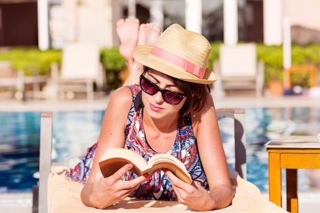 Mulher lendo um livro enquanto estava deitado em uma rede