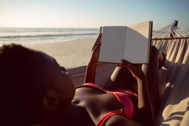 Mulher, lendo um livro, enquanto, relaxante, em, rede, praia