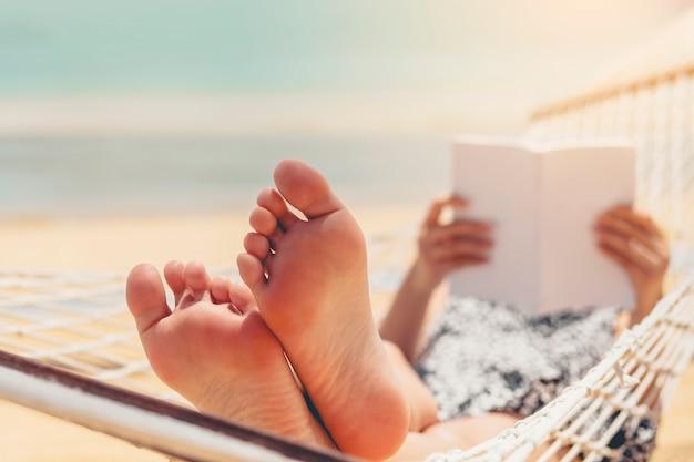 Mulher, lendo um livro, ligado, rede, praia, em, tempo livre, verão, feriado