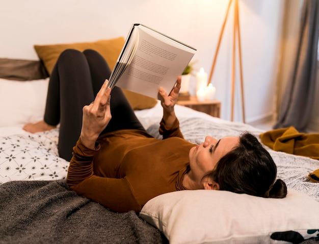 Mulher lendo um livro na cama de costas