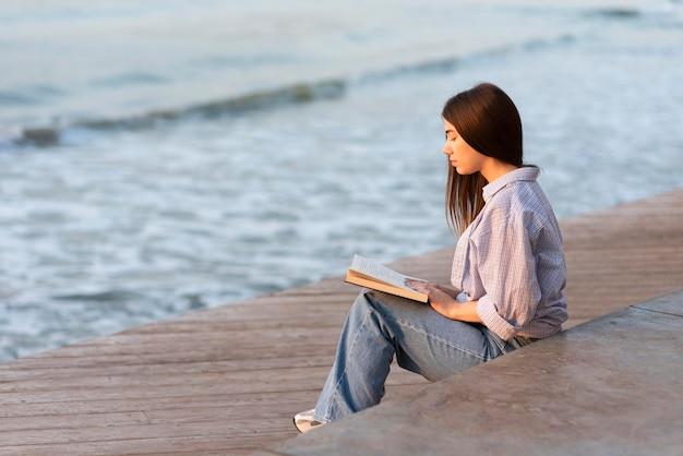 Mulher lendo um livro na praia de vista lateral