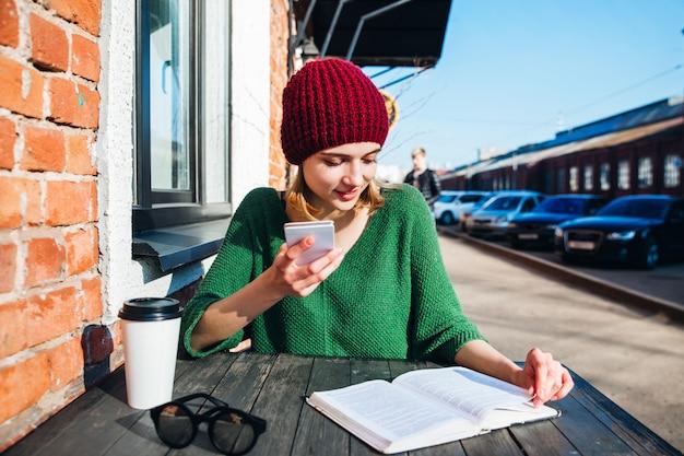 Mulher lendo um livro no terraço do café