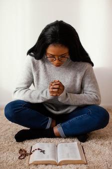 Mulher lendo um livro sagrado dentro de casa