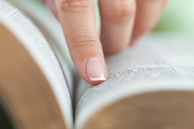 Mulher lendo um livro velho e pesado no fundo, close-up