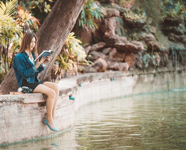 Mulher lendo uma educação de livro no parque usando uma mini saia perto do lado do rio.