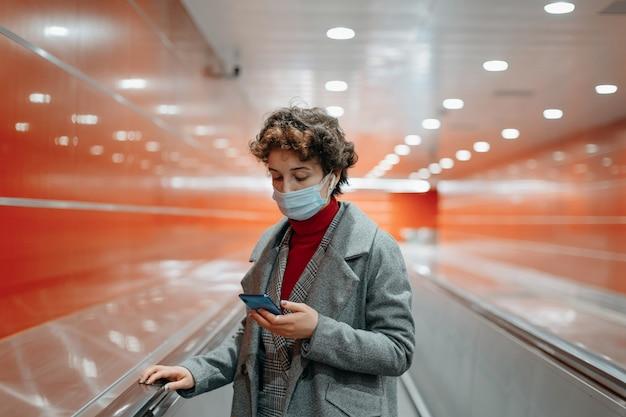 Mulher lendo uma mensagem em uma plataforma de metrô