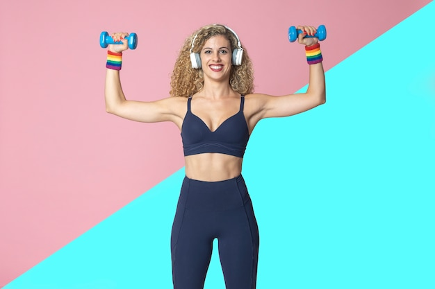 Mulher lésbica com prática de esporte estilo de vida fitness realiza exercícios de treinamento com pesos, ouvindo música com fones de ouvido