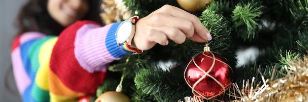Mulher lésbica pendurando bolas de natal na árvore e sorrindo, close-up