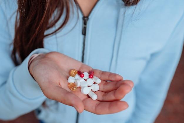 Mulher leva e mostra os comprimidos.