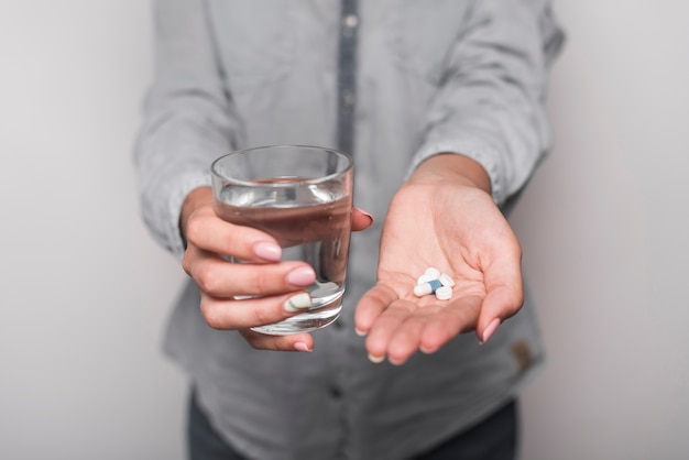 Mulher, levando, medicina, segurando, vidro água