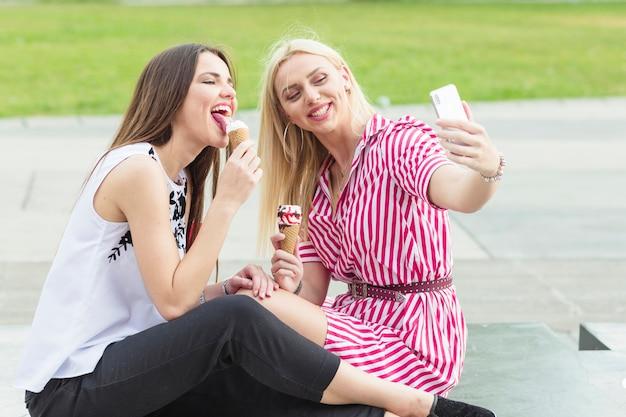 Mulher, levando, selfie, enquanto, dela, amigo, lamber, icecream, com, cellphone