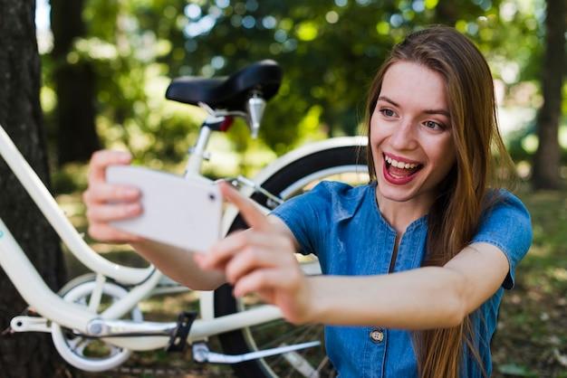 Mulher, levando, selfie, perto, bicicleta