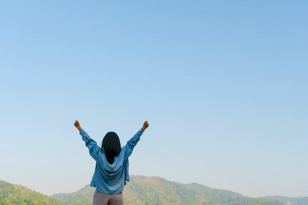 Mulher levanta as mãos ao conceito de liberdade do céu com céu azul e fundo de montanha de campo de verão.