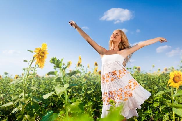Mulher levanta as mãos para o céu no campo de flores
