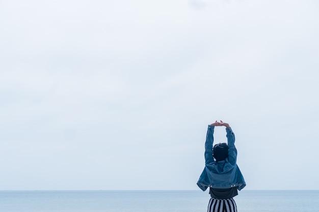 Mulher levanta as mãos para o conceito de liberdade do céu com céu do sol e temporada de verão na praia.