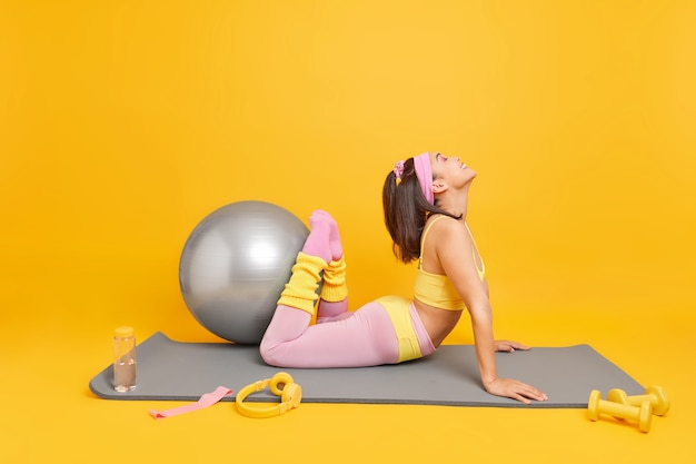 Mulher levanta as pernas mostra sua flexibilidade usa top recortado e leggings poses no tapete de fitness faz exercícios com bola suíça se sente feliz isolada no amarelo