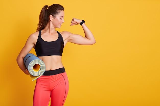 Mulher levanta o braço e mostrando os músculos após o treino, segurando karemat, gosto de malhar na academia com o treinador, veste roupas esportivas