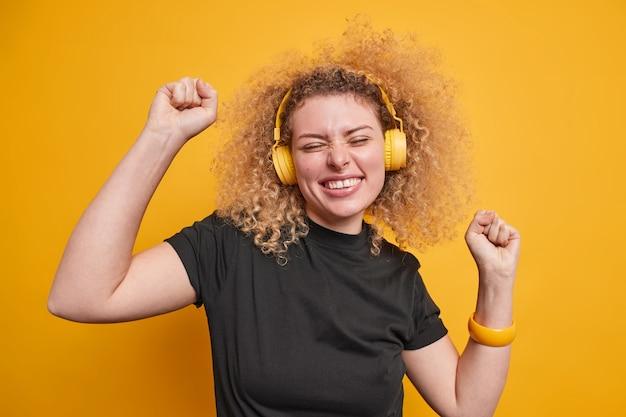 Mulher levanta os braços sente danças animadas com ritmo de música arrepios dentro de casa usa fones de ouvido estéreo, camiseta preta casual