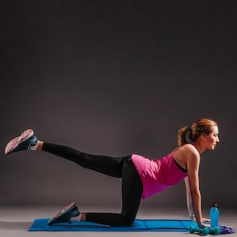 Mulher, levantamento, perna esquerda, ligado, esticando esteira