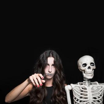 Mulher levantando a mão perto do esqueleto