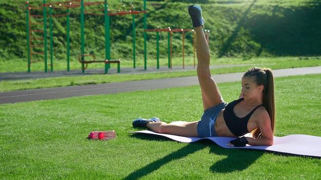Mulher levantando a perna na grama