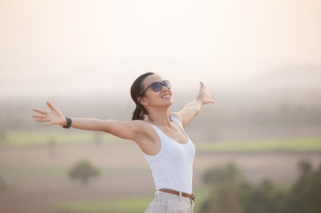Mulher levantando as mãos no topo de uma montanha durante uma caminhada e postes em pé no cume de uma montanha rochosa, olhando os vales.