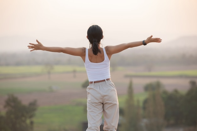 Mulher levantando as mãos no topo de uma montanha durante uma caminhada e postes em pé no cume de uma montanha rochosa, olhando para vales e picos.