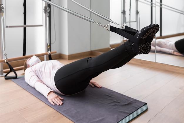 Mulher levantando as pernas na aula de pilates. deitado no chão e puxando com os pés em algumas molas