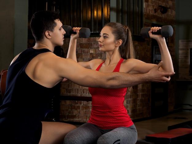 Mulher levantando halteres com seu personal trainer no ginásio.
