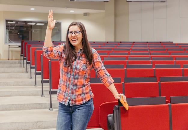 Mulher levantando mão no anfiteatro da universidade