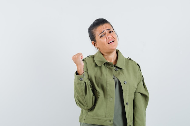 Mulher levantando o punho cerrado em jaqueta, camiseta e parecendo triste