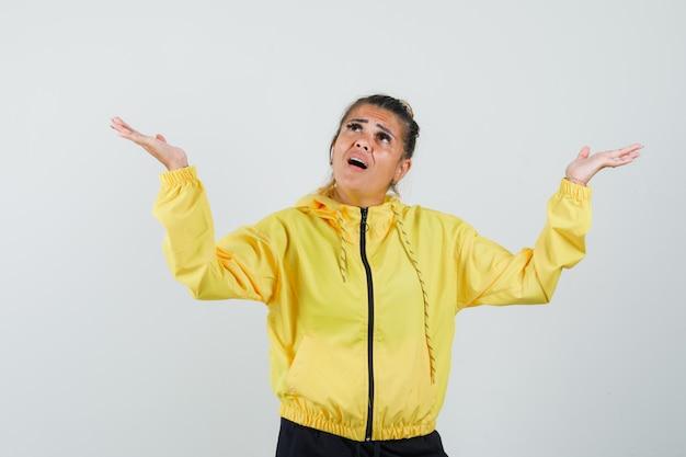 Mulher levantando os braços enquanto olha para cima em um terno esporte e parece confusa, vista frontal.
