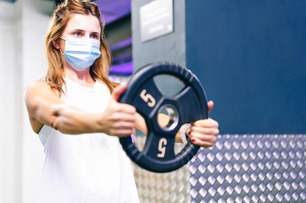 Mulher levantando peso na academia com uma máscara