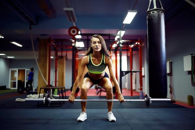 Mulher levantando um crossfit de peso no ginásio
