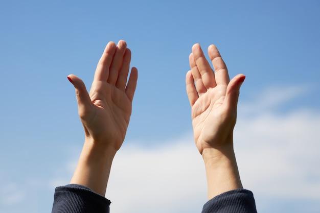 Mulher levantou as mãos e pede a deus que dê saúde a seus amados