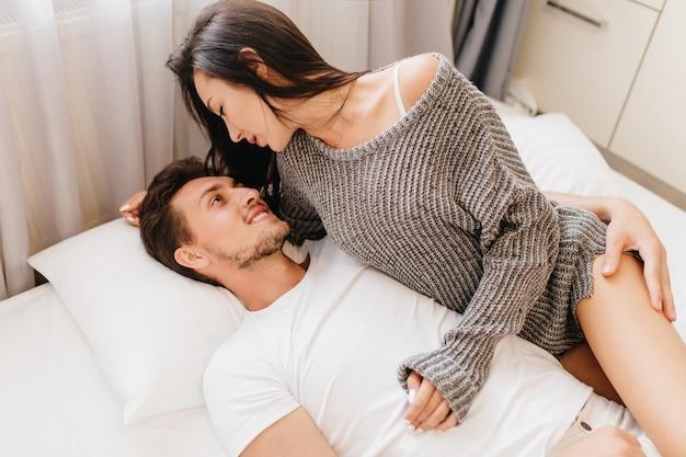 Mulher levemente bronzeada com cabelo preto se divertindo com o marido na manhã de domingo