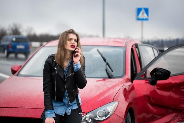 Mulher liga para um serviço ao lado de um carro vermelho