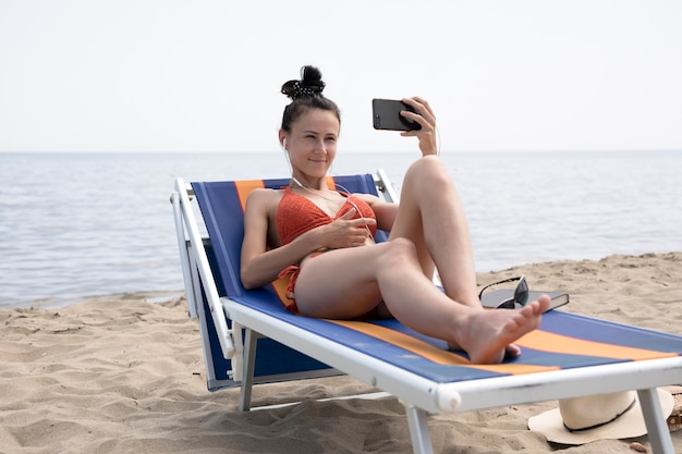 Mulher, ligado, cadeira praia, levando, um, selfie