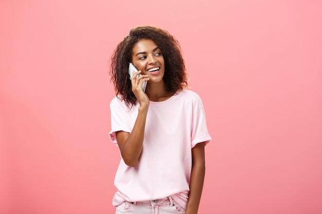 Mulher ligando para namorado, venha buscá-la após o treino em pé na rua despreocupada e tranquila olhando para a direita com um largo sorriso satisfeito segurando o smartphone perto da orelha posando sobre a parede rosa