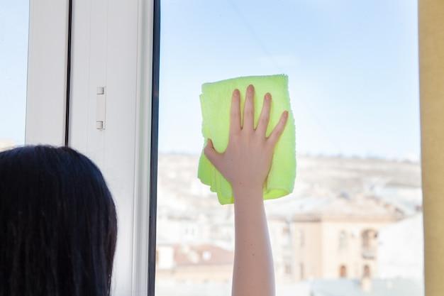 Mulher limpa a janela com um pano