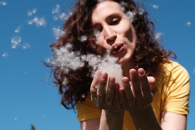 Mulher limpa as mãos com penugem de choupo
