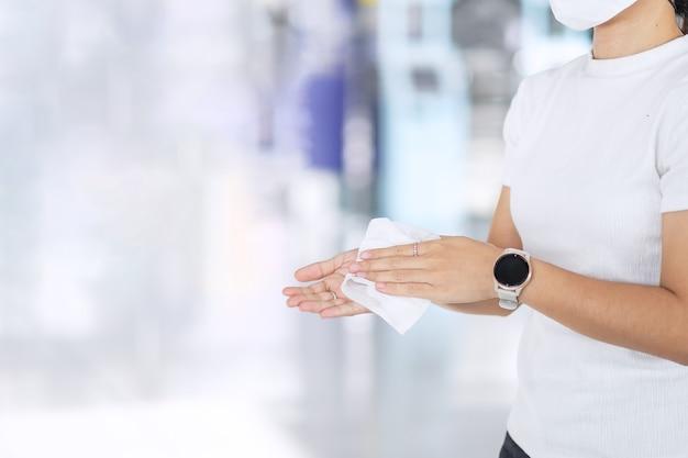 Mulher limpa as mãos com um lenço úmido após contrair algo no transporte público
