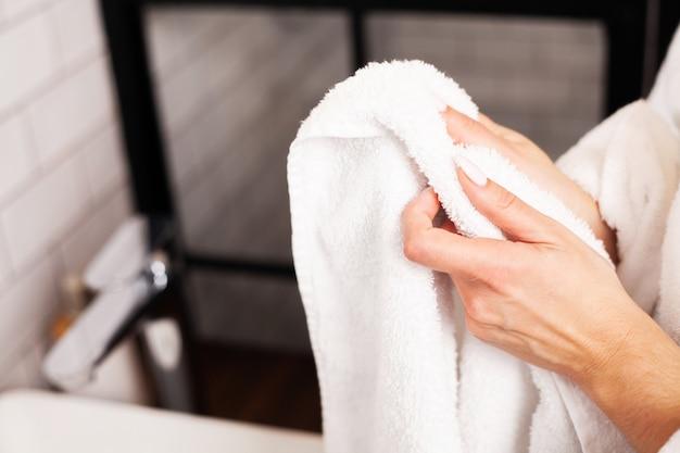 Mulher limpa as mãos em uma toalha em uma casa de banho brilhante