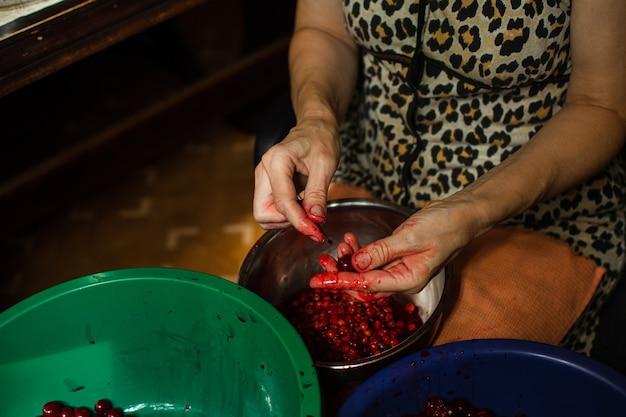 Mulher limpa as sementes das cerejas antes de cozinhar