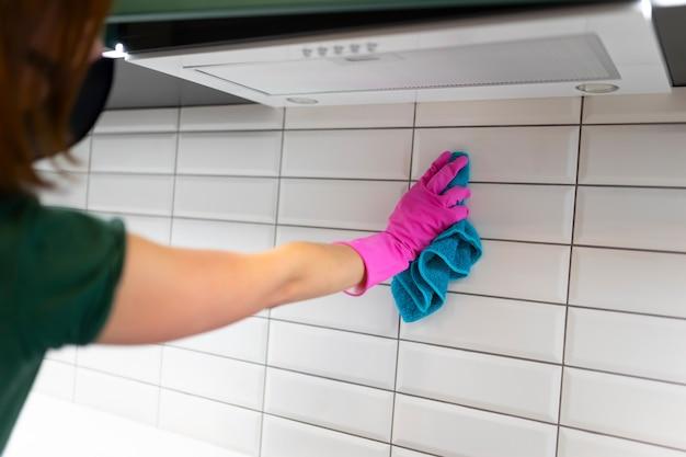 Mulher limpa azulejos na cozinha