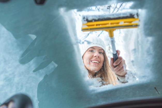 Mulher limpa carro de neve vista de dentro