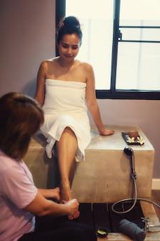 Mulher limpa e lave os pés no spa